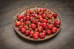 Куча зрелой свежей красной вишни в коричневом керамическом блюде деревянное предпосылки деревенское Стоковая Фотография RF