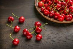 Куча зрелой свежей сладостной вишни в плите глины и разбросанной на деревенский деревянный стол Стоковое Фото