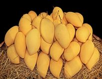 Куча зрелых манго с соломой на черной предпосылке Стоковые Фото