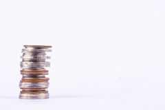 Куча изолированных денег стогов монеток на белом деле финансов предпосылки Стоковые Фото