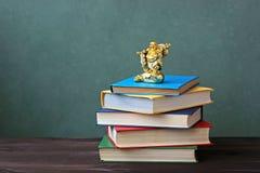 Куча книг в крышках цвета и netsuke (куче книг в co Стоковые Фото