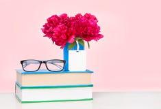 Куча книг и вазы цветков на деревянном столе стоковая фотография