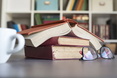 Куча книг с стеклами чтения на столе Стоковая Фотография RF