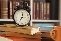 Куча книг с o& x27; часы на столе Стоковое Фото