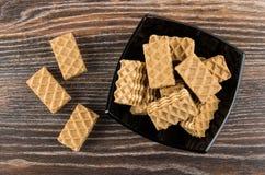 Куча коричневых вафель в черном шаре и на таблице Стоковая Фотография RF