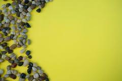 Куча коричневых камешков на желтой предпосылке стоковые изображения rf