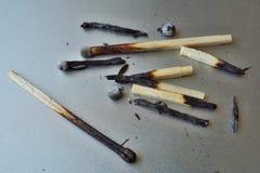 Куча, который сгорели спичек и золы на серебряной предпосылке как символ высасывания, расхода и разрушения Стоковые Фото