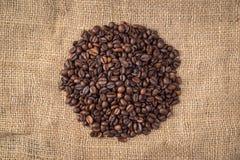 Куча кофейных зерен в середине на предпосылке джута Стоковая Фотография