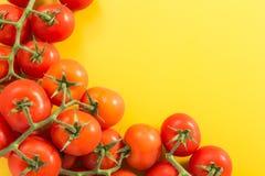 Куча красных томатов вишни с стержнем, на желтой предпосылке с экземпляр-космосом Стоковые Изображения