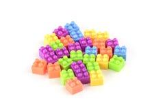 Куча красочных пластичных кирпичей игрушки на белой предпосылке Стоковые Фото