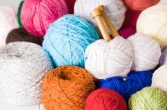 Куча красочных шариков пряжи, белизна крупного плана, синь, пинк, фиолетовый и коричневый с деревянными вязать иглами в середине Стоковые Изображения