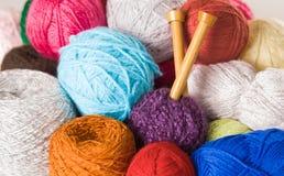 Куча красочных шариков пряжи, белизна крупного плана, синь, пинк, фиолетовый и коричневый с деревянными вязать иглами в середине Стоковое Изображение