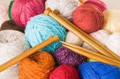 Куча красочных шариков пряжи, белизна крупного плана, синь, пинк, фиолетовый и коричневый с деревянными вязать иглами в середине Стоковая Фотография