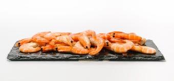 Куча креветок в раковине льда на плите черного сланца на белом backg Стоковое Изображение RF