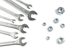 Куча ключей различных размеров против гаек различных размеров изолированных на белизне Стоковая Фотография RF