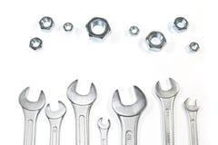 Куча ключей различных размеров против гаек различных размеров изолированных на белизне Стоковое фото RF