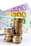 Куча монеток евро на примечаниях евро Стоковые Изображения