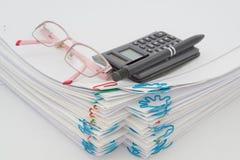 Куча обработки документов имеет ручку с зрелищами и калькулятором Стоковые Фото