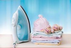 Куча одежд ` s детей и утюга на таблице стоковые фотографии rf