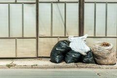 Куча отброса и домашнего старья вышла в фронт дома в улице в полиэтиленовых пакетах для тележки dumper для того чтобы собрать стоковое фото