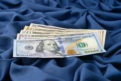 Куча долларовых банкнот на голубой предпосылке ткани Стоковое Изображение