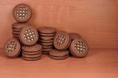 Куча печений обломока шоколада заполнила с ванильными белыми cream лож на деревянной коричневой поверхности Biscu сладостного и в Стоковое Изображение RF