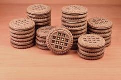 Куча печений обломока шоколада заполнила с ванильными белыми cream лож на деревянной коричневой поверхности Biscu сладостного и в Стоковые Изображения