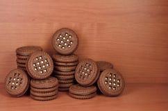 Куча печений обломока шоколада заполнила с ванильными белыми cream лож на деревянной коричневой поверхности Biscu сладостного и в Стоковые Фото