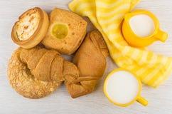 Куча печенья, салфетки, чашки молока на деревянном столе Стоковое фото RF