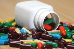 Куча пилюлек витамина с капсулой в белой бутылке Стоковые Фото