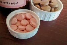 Куча пилюлек утюга и витамина b12 внутри крышек их бутылок Стоковое Изображение RF
