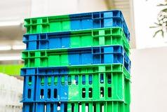 Куча пластичных паллетов голубых и серого цвета штабелированная около магазина Стоковые Фото