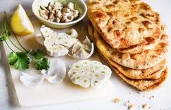 Куча плоских хлеба и специй на таблице Стоковые Изображения