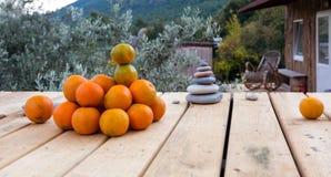 Куча плодоовощей апельсина и столбца каменных камешков на деревянном поле Стоковое фото RF