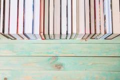 Куча различных книг на деревянной предпосылке Стоковое Фото