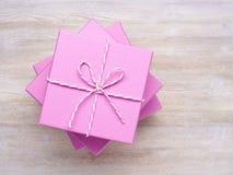 Куча розовых коробок взгляд сверху подарков на белом деревянном backgroun Стоковая Фотография