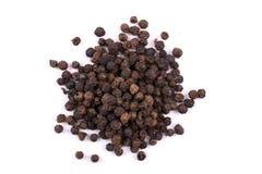 Куча семян сухих черного перца изолированных на белизне Стоковые Фото