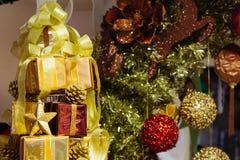 Куча сияющих подарочных коробок украшенных в рождественской елке с украшениями орнамента рождества на заднем плане Стоковое Изображение RF