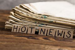 Куча старых газет около квадратов прямоугольника картона с самой новостью рукописной надписи на старом коричневом деревянном стол стоковая фотография
