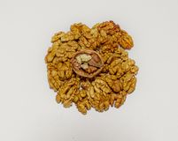 Куча стерженей грецкого ореха и треснутого грецкого ореха на верхней части на белизне Стоковые Изображения