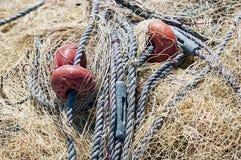 Куча сушить желтую рыболовную сеть с красными поплавками стоковое изображение