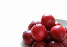 Куча сливы зрелого залива рубиновой приносить на плите изолированной на белизне Стоковые Фото