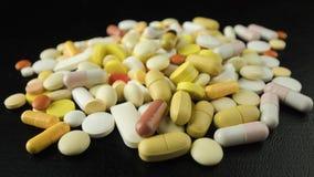 Куча таблеток и лож капсул на черной предпосылке Концепция злоупотребления наркотиками стоковые изображения