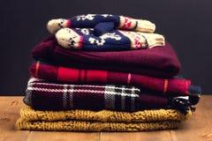Куча теплых и уютных зимы и осени одевает на деревянных тонизированных mittens шарфа кардиганов свитеров предпосылки Стоковая Фотография