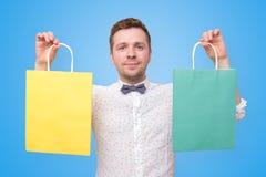 Куча удерживания человека сумок с усмехаться подарков стоковая фотография