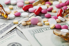 Куча фармацевтических пилюлек лекарства и медицины разбросала на деньги наличных денег доллара, продукт цены целебный и концепцию стоковая фотография rf