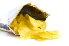 Куча хрустящих корочек картошки на белизне Стоковые Фото