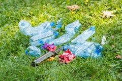 Куча хлама на траве в парке, засаривать окружающей среды Стоковое Изображение RF