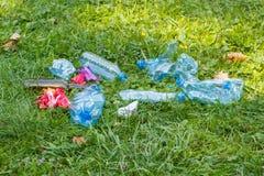 Куча хлама на траве в парке, засаривать окружающей среды Стоковое Изображение