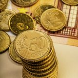 Куча 50 центов евро лежит на бумажном счете 50 евро Стоковая Фотография